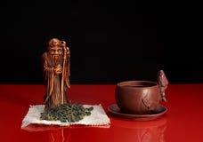 1 ζωή ακόμα Statuette πνεύμα τσαγιού, πράσινο τσάι, πιατικά Στοκ φωτογραφίες με δικαίωμα ελεύθερης χρήσης