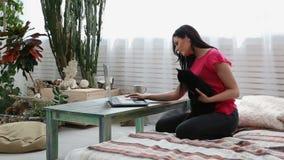Ζωή με τα κατοικίδια ζώα το όμορφο κορίτσι εργάζεται στο σπίτι σε ένα lap-top με μια μαύρη γάτα σε ετοιμότητα της απόθεμα βίντεο