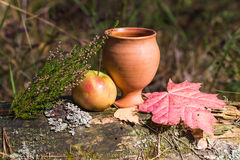ζωή φθινοπώρου ακόμα ένα μήλο και ένα κόκκινο φλυτζανιών αργίλου φεύγουν Στοκ φωτογραφία με δικαίωμα ελεύθερης χρήσης