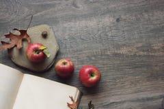 Ζωή φθινοπώρου ακόμα με τρία μήλα, το ανοικτά βιβλίο και τα φύλλα πέρα από το αγροτικό ξύλινο υπόβαθρο Στοκ φωτογραφία με δικαίωμα ελεύθερης χρήσης
