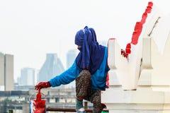 Ζωγράφος γυναικών με την μπλε μάσκα που χρωματίζει το κόκκινο χρώμα στο υψηλό κτήριο Στοκ εικόνες με δικαίωμα ελεύθερης χρήσης
