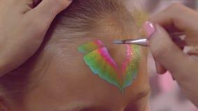 Ζωγράφος γυναικών που χρωματίζει το πολύχρωμο aquagrum στο πρόσωπο κοριτσιών κοντά επάνω φιλμ μικρού μήκους
