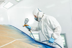 Ζωγράφος επισκευαστών στην αίθουσα που χρωματίζει τον αυτοκινητικό προφυλακτήρα αυτοκινήτων Στοκ Εικόνες