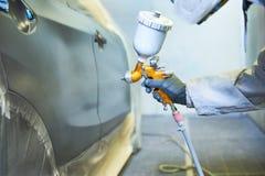 Ζωγράφος επισκευαστών στην αίθουσα που χρωματίζει το αυτοκινητικό καπό αυτοκινήτων Στοκ Εικόνες