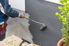 Ζωγράφος με τον κύλινδρο χρωμάτων υπό εξέταση Στοκ Εικόνες