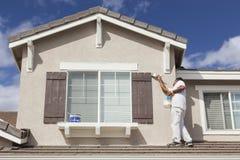 Ζωγράφος σπιτιών που χρωματίζει την περιποίηση και τα παραθυρόφυλλα του σπιτιού στοκ εικόνες