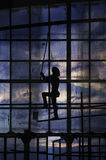 Ζωγραφική ατόμων στον τοίχο παραθύρων γυαλιού με τον κύλινδρο χρωμάτων πέρα από το ηλιοβασίλεμα Στοκ φωτογραφίες με δικαίωμα ελεύθερης χρήσης