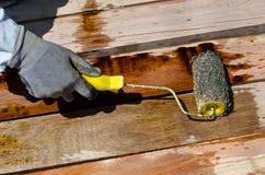 Ζωγραφική βουρτσών εκμετάλλευσης χεριών εργαζομένων στο ξύλο Στοκ Εικόνα