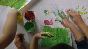 Ζωγραφική δάχτυλων χεριών παιδιών με τα διάφορα χρώματα φιλμ μικρού μήκους