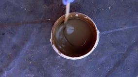 Ζωγραφική και επισκευές - το χρώμα στον κάδο ανακατώνεται με ένα ραβδί φιλμ μικρού μήκους