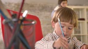 Ζωγραφική μικρών παιδιών σε χαρτί και χαμόγελο, εύθυμο όταν ο πατέρας του που μιλά στο τηλέφωνο στο υπόβαθρο, που κάθεται σε σύγχ απόθεμα βίντεο