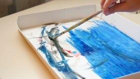 Ζωγραφική παιδιών χεριών με τα watercolors σε χαρτί Τα χρώματα παιδιών με το watercolor απόθεμα βίντεο