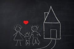 Ζωγραφική παιδιών ` s στον πίνακα κιμωλίας οικογενειακή κατοικί&alpha Στοκ Εικόνες