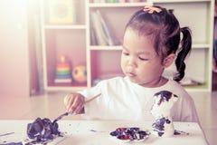 Ζωγραφική παιδιών, μικρό κορίτσι που έχει τη διασκέδαση για να χρωματίσει στην κούκλα στόκων Στοκ Εικόνα