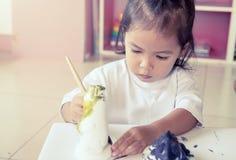 Ζωγραφική παιδιών, μικρό κορίτσι που έχει τη διασκέδαση για να χρωματίσει στην κούκλα στόκων Στοκ Φωτογραφία