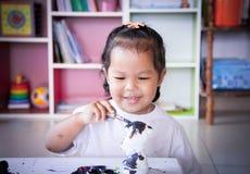 Ζωγραφική παιδιών, μικρό κορίτσι που έχει τη διασκέδαση για να χρωματίσει στην κούκλα στόκων Στοκ Εικόνες