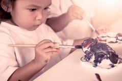 Ζωγραφική παιδιών, μικρό κορίτσι που έχει τη διασκέδαση για να χρωματίσει στην κούκλα στόκων Στοκ Φωτογραφίες