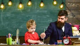 Ζωγραφική πατέρων και γιων μαζί στο δωμάτιο μελέτης Οικογένεια στα πολυάσχολα πρόσωπα που δημιουργούν, σχεδιασμός Δάσκαλος και πα στοκ φωτογραφία με δικαίωμα ελεύθερης χρήσης