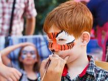 Ζωγραφική προσώπου αγοριών παιδιών, που κάνει τη διαδικασία ματιών τιγρών Στοκ Εικόνα