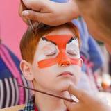 Ζωγραφική προσώπου αγοριών παιδιών, που κάνει τη διαδικασία ματιών τιγρών Στοκ Φωτογραφία