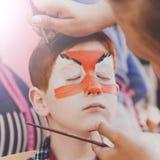Ζωγραφική προσώπου αγοριών παιδιών, που κάνει τη διαδικασία ματιών τιγρών Στοκ φωτογραφία με δικαίωμα ελεύθερης χρήσης