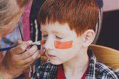 Ζωγραφική προσώπου αγοριών παιδιών, που κάνει τη διαδικασία ματιών τιγρών Στοκ εικόνες με δικαίωμα ελεύθερης χρήσης