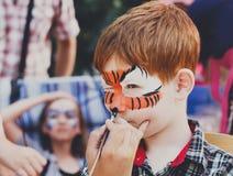 Ζωγραφική προσώπου αγοριών παιδιών, που κάνει τη διαδικασία ματιών τιγρών Στοκ Εικόνες
