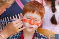 Ζωγραφική προσώπου αγοριών παιδιών, που κάνει τη διαδικασία ματιών τιγρών Στοκ εικόνα με δικαίωμα ελεύθερης χρήσης