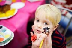 Ζωγραφική προσώπου για το χαριτωμένο μικρό παιδί κατά τη διάρκεια της γιορτής γενεθλίων παιδιών Στοκ Εικόνες