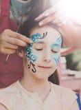 Ζωγραφική προσώπου κοριτσιών, που κάνει τη διαδικασία πεταλούδων Στοκ εικόνα με δικαίωμα ελεύθερης χρήσης