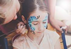 Ζωγραφική προσώπου κοριτσιών, που κάνει τη διαδικασία πεταλούδων Στοκ εικόνες με δικαίωμα ελεύθερης χρήσης