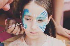 Ζωγραφική προσώπου κοριτσιών, που κάνει τη διαδικασία πεταλούδων Στοκ Φωτογραφία