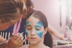 Ζωγραφική προσώπου κοριτσιών, που κάνει τη διαδικασία πεταλούδων Στοκ Φωτογραφίες