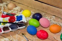 Ζωγραφική των ζωηρόχρωμων αυγών για Πάσχα στο αγροτικό ξύλινο υπόβαθρο στοκ εικόνες