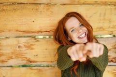 Ζωηρή redhead υπόδειξη γέλιου στη κάμερα Στοκ Εικόνα