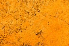 Ζωηρός φωτεινός πορτοκαλής τοίχος πετρών προσόψεων χρώματος με τις ατέλειες και ρωγμές ως κενό αγροτικό και απλό υπόβαθρο στοκ εικόνα