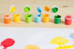 Ζωηρόχρωμα ακρυλικά χρώματα στον ξύλινο πίνακα Τέχνη παιδιών ` s Στοκ φωτογραφία με δικαίωμα ελεύθερης χρήσης