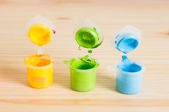 Ζωηρόχρωμα ακρυλικά χρώματα στον ξύλινο πίνακα Τέχνη παιδιών ` s Στοκ Εικόνες