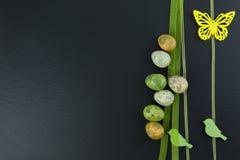 Ζωηρόχρωμα αυγά ορτυκιών και κίτρινα πράσινων ξύλινα πουλιά πεταλούδων και στον πίνακα πετρών Τοπ άποψη με το διάστημα αντιγράφων στοκ φωτογραφίες