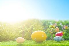 Ζωηρόχρωμα αυγά Πάσχας και ένα μεγάλο κίτρινο αυγό Πάσχας στην πράσινη χλόη άνοιξη Στοκ φωτογραφία με δικαίωμα ελεύθερης χρήσης