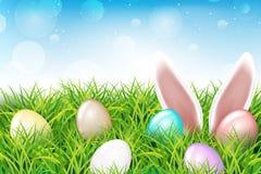 Ζωηρόχρωμα αυγά Πάσχας και αυτιά κουνελιών που κολλούν έξω τη χλόη Στοκ Φωτογραφία