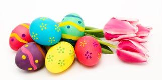 Ζωηρόχρωμα αυγά Πάσχας και λουλούδια που απομονώνονται σε ένα λευκό Στοκ φωτογραφία με δικαίωμα ελεύθερης χρήσης