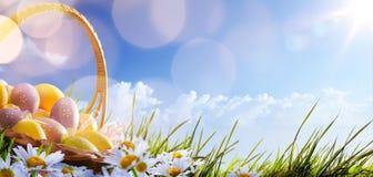 Ζωηρόχρωμα αυγά Πάσχας με τα λουλούδια στη χλόη στο μπλε Στοκ Φωτογραφίες