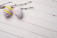 Ζωηρόχρωμα αυγά Πάσχας με τους κλάδους της πασχαλιάς Στοκ Εικόνες