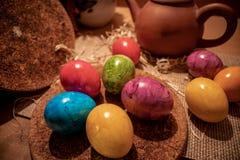 Ζωηρόχρωμα αυγά Πάσχας με το ξύλινο υπόβαθρο στοκ εικόνα