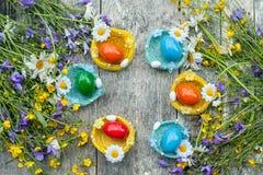 Ζωηρόχρωμα αυγά Πάσχας που βρίσκονται στα ψάθινα πιάτα υπό μορφή φωλιάς στο ξύλινο υπόβαθρο με μια ανθοδέσμη των άγρια περιοχών Στοκ Εικόνα