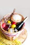 Ζωηρόχρωμα αυγά Πάσχας σε ένα καλάθι με το κέικ, το κόκκινο κρασί, hamon ή το jerky και ξηρό καπνισμένο λουκάνικο στο άσπρο υπόβα Στοκ φωτογραφία με δικαίωμα ελεύθερης χρήσης