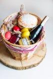Ζωηρόχρωμα αυγά Πάσχας σε ένα καλάθι με το κέικ, το κόκκινο κρασί, hamon ή το jerky και ξηρό καπνισμένο λουκάνικο στο άσπρο υπόβα Στοκ Εικόνες