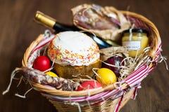 Ζωηρόχρωμα αυγά Πάσχας σε ένα καλάθι με το κέικ, το κόκκινο κρασί, hamon ή το jerky και ξηρό καπνισμένο λουκάνικο στο ξύλινο υπόβ Στοκ Εικόνες