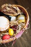 Ζωηρόχρωμα αυγά Πάσχας σε ένα καλάθι με το κέικ, το κόκκινο κρασί, hamon ή το jerky και ξηρό καπνισμένο λουκάνικο στο ξύλινο υπόβ Στοκ φωτογραφία με δικαίωμα ελεύθερης χρήσης